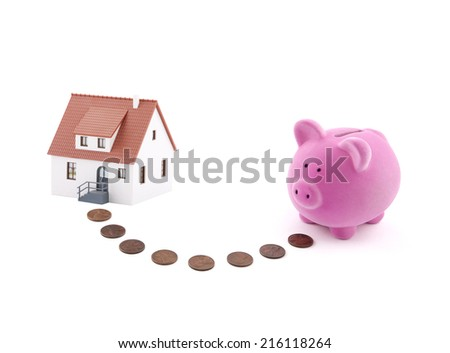 Saving for a house. Piggy bank with coins and house miniature. - stock photo