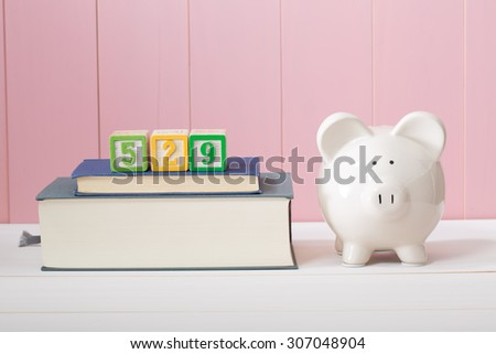 Saving for the costs of education with 529 plan concept with  piggy bank standing alongside stacked textbooks - stock photo
