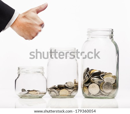 Saving for your future-Coins in clear bottle over white background