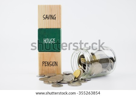Saving, house and pension word on wooden block with coins in glass jar. Financial concept - stock photo
