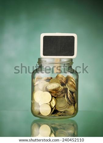 saving jar with the small black board - stock photo