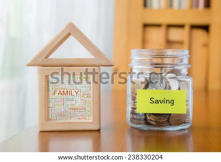 Saving label on money jar and wooden home  blocks with house and family word cloud - stock photo
