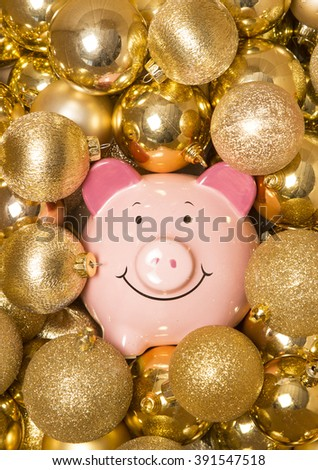 Saving money at christmas piggybank on gold baubles