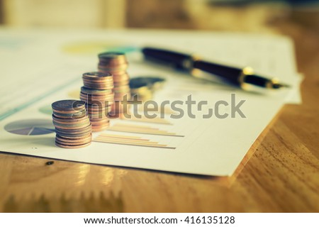Saving money concept,graph, stacks of coins ,chart and pen ,copy space.selective focus,vintage color