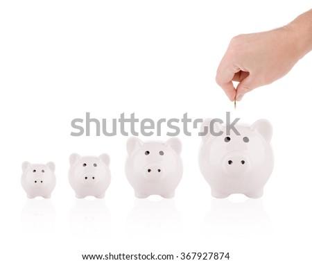 Saving money concept - Growing savings. Hand putting coin into piggy bank - stock photo