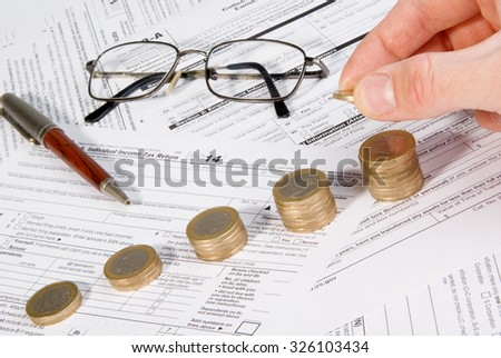 Saving money concept - Growing savings. Male hand putting money on growing coin stack - stock photo