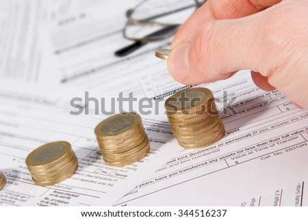 Saving money concept - Growing savings. Male hand putting money on growing coin stack