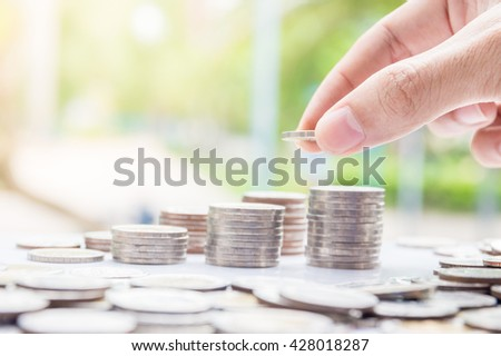 Saving money concept. Hand of the man putting money coin stack growing business.