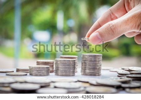 Saving money concept. Hand of the man putting money coin stack growing business.Vignetting