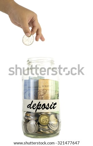 Saving money concept. Kid hand putting a coin into a glass jar with tagging 'deposit' on masking tape isolated on white background.
