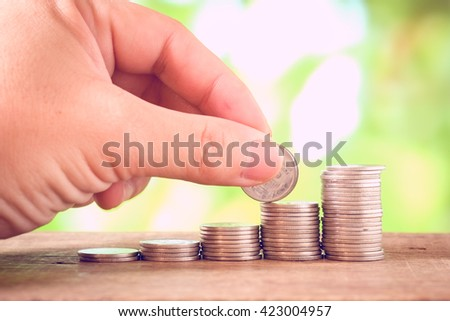 Saving money concept,Male hand putting money coin stack growing business with filter effect retro vintage style