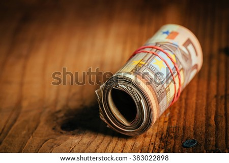 Saving money concept, rolled up cash with rubber band on wooden desk, fifty euro banknotes as personal home budget stack, selective focus - stock photo