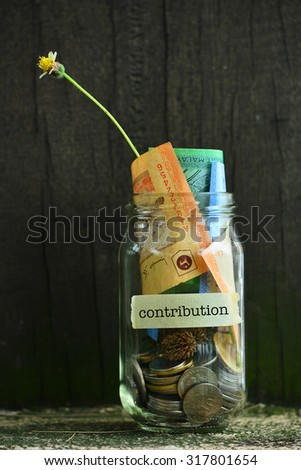 Saving Money Concept With Contribution Text Written Label On Glass Jar.Selective Focus And Shallow DOF. - stock photo
