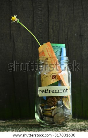 Saving Money Concept With Retirement Text Written Label On Glass Jar.Selective Focus And Shallow DOF. - stock photo