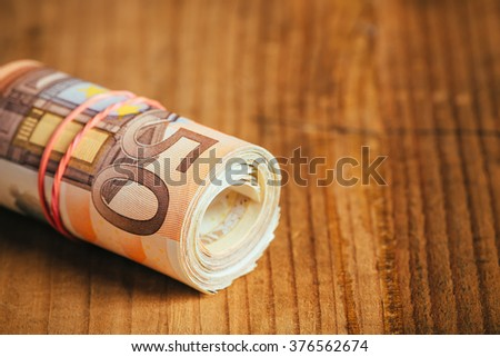 Saving money concept with rolled up cash, fifty euro banknotes, selective focus - stock photo