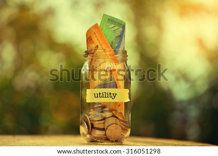 Saving Money Concept With Utility Text Written Label On Glass Jar.Selective Focus And Shallow DOF. - stock photo