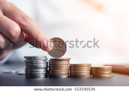 Saving money. Female hand stack coins to shown concept of growing business and wealthy.