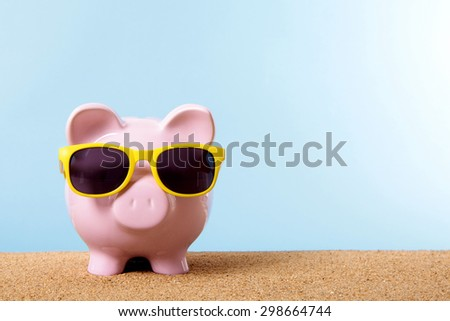 Saving money for vacation or retirement, Piggy bank on beach, sunglasses.  Copy space.