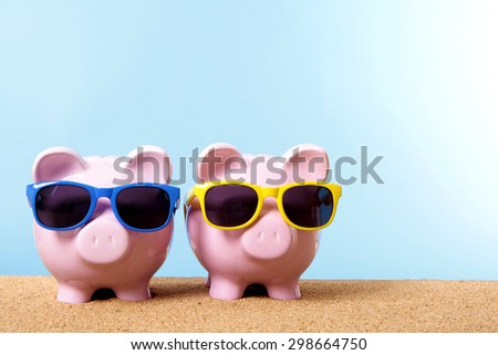 Saving money for vacation, two piggy banks on beach with sunglasses.  Copy space.