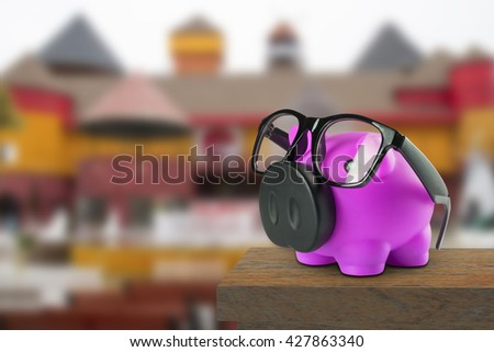 Saving money, Piggy Bank and Coin in Female Hands over Green Grass on abstract blurred background,Saving to buy a house, real estate or home savings, piggy bank in front of property