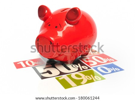 Saving money - red piggy bank on multicolored newspaper percentage advertisements - stock photo