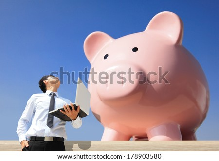 Saving Money with my piggy bank - Young business man look to piggy bank with computer - stock photo