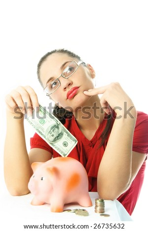 saving money-young thoughtful woman putting money into a pink  piggy bank
