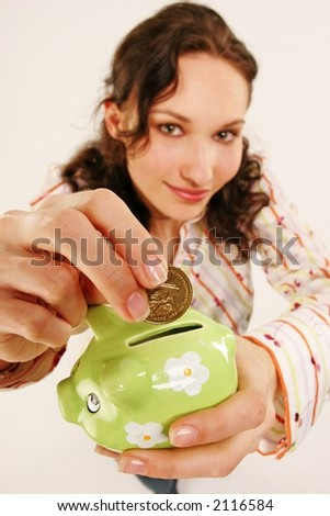 saving money-young woman putting a coin into a green money-box