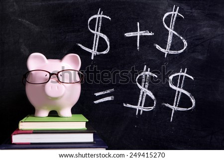 Saving plan : Pink piggy bank with glasses standing on books next to a blackboard with simple money savings plan.  Investment plan, growth concept. - stock photo