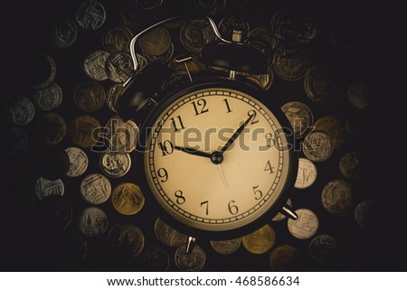 saving time, Alarm clock with coins isolated on black background. with vintage filter