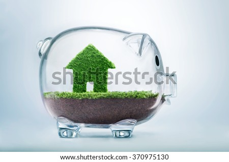 Saving to buy a house or home savings concept with grass growing in shape of house inside transparent piggy bank - stock photo