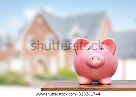 Saving to buy a house, real estate or home savings, piggy bank in front of property - stock photo
