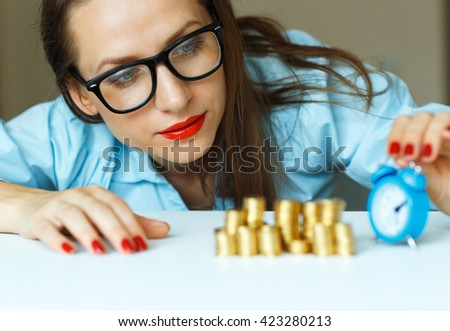 Saving, woman stacking gold coins into columns