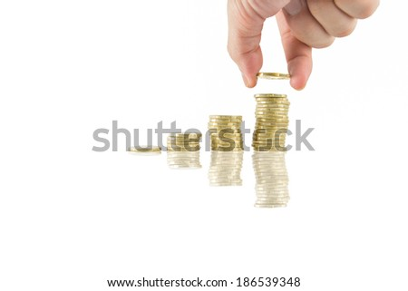 Savings close up of male hand stacking golden coins on white background
