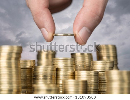 Savings, close up of male hand stacking golden coins over sky background - stock photo