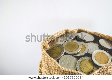 Savings coins in sack with white background. Stock asset investment, Retirement plan, Pension fund, 401K, Passive income, Millionaire, Financial freedom and wealth increment, Budget and tax concept.
