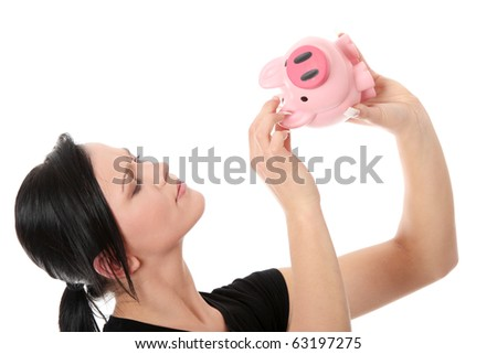 Savings concept - a woman with a piggy bank trying to get out some money - isolated over white - stock photo