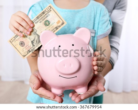 Savings concept. Child putting dollar in the piggy bank, close up