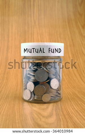 savings concept, coins in jar with mutual fund label on wooden background. - stock photo