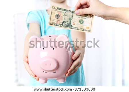Savings concept. Hand putting dollar in the piggy bank, close up