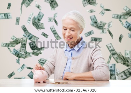 savings, finances, annuity insurance, retirement and people concept - smiling senior woman putting coins into piggy bank over money rain background - stock photo