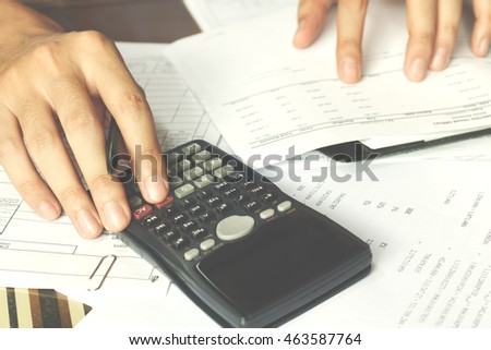 savings, finances, economy and office concept. Business people counting on calculator sitting at the table. Close up of hands and stationery, soft focus