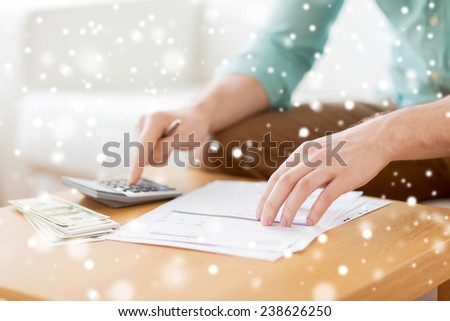 savings, finances, paperwork and people concept - close up of man with calculator counting money and making notes at home - stock photo