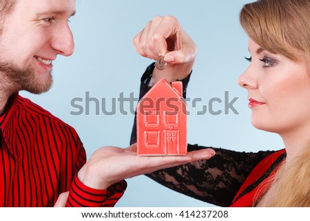 Savings for future plans. Couple with red little house piggy bank and silver coin. Money loin for family home better life.