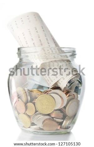 Savings jar full with coins and bills - stock photo