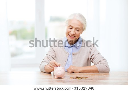 savings, money, annuity insurance, retirement and people concept - smiling senior woman putting coins into piggy bank at home - stock photo
