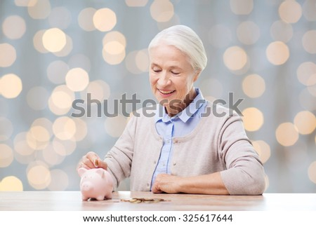 savings, money, annuity insurance, retirement and people concept - smiling senior woman putting coins into piggy bank over holidays lights background - stock photo