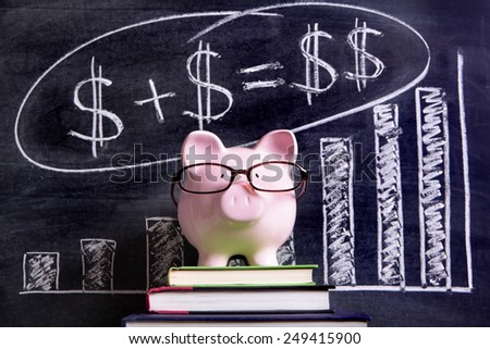 Savings plan : Pink piggy bank with glasses standing on books next to a blackboard with simple money savings plan chart.  Piggybank savings collection. - stock photo