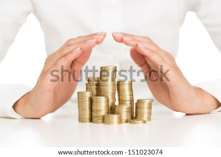 Savings protection, close up of female hands covering stack of golden coins - stock photo