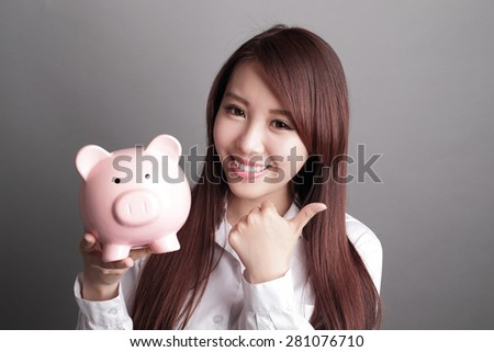 Savings woman smiling happy and holding pink piggy bank isolated on gray background. Asian girl - stock photo
